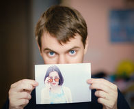 Man holding a photo of a girl. Royalty Free Stock Photo