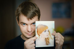 Man holding a photo of a girl. Stock Images