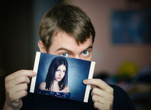 Man holding a photo of a girl. Royalty Free Stock Image