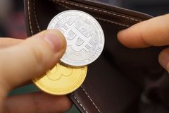 Bitcoins. Man holding physical version of golden and silver bitcoins stock photo