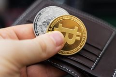 Bitcoins. Man holding physical version of golden and silver bitcoins stock images