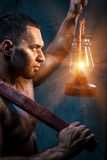 Man holding pickaxe and oil lamp. Muscular man holding pickaxe and oil lamp royalty free stock photo