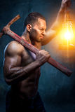 Man holding pickaxe and oil lamp. Muscular man holding pickaxe and oil lamp royalty free stock photos