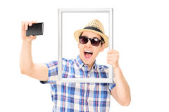 Man holding a picture frame and taking selfie Stock Images
