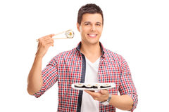 Man holding a piece of sushi on Chinese sticks Royalty Free Stock Photography