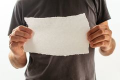 Man holding piece of torn blank paper as copy space. For text message Royalty Free Stock Photo
