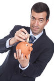 Man holding a piggy bang and putting bills inside Royalty Free Stock Photography