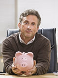 Man Holding Piggy Bank Stock Image