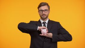 Man holding piggy-bank, banking investment and finance, caring about future. Stock footage stock video footage