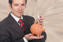 Man  holding a piggy bank and dollar bills Royalty Free Stock Images