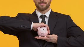 Man holding piggy-bank on isolated background, financial transactions, deposits