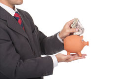 Man holding piggy bank and putting dollars inside Stock Photos