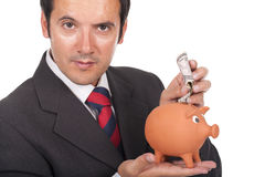 Man holding piggy bank and putting dollars inside Stock Photo