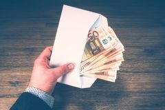 Man holding pile of 50 euro banknotes in envelope. Finances and. Man holding pile of 50 euro banknotes in white envelope. Finances and budget concept Royalty Free Stock Photography