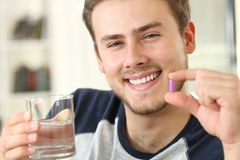 Man holding a pill looking at camera Royalty Free Stock Images