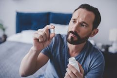 Man holding pill. Mid adult man holding pill in the hand sitting on the bed at home royalty free stock images