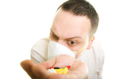 Man holding pills. Insecure man with a mask holding pills Stock Images