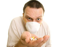 Man holding pills. The man with the mask holding pills Stock Photos