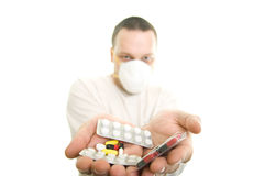 Man holding pills. The man with the mask holding pills Stock Photography