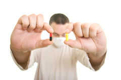 Man holding pills. The man with the mask holding pills Royalty Free Stock Photos