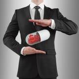 Man holding pills. Businessman holding pills with dollar sign Stock Photo
