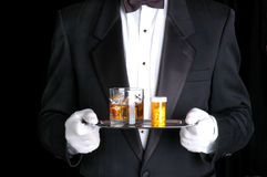 Man Holding Pills and Cocktail on Silver Tray royalty free stock photos