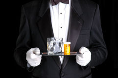 Man Holding Pills and Glass of Water on Silver Tray royalty free stock photo