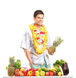 Man holding a pinneapple and posing behind a table with fruits a Royalty Free Stock Images