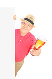 Man holding a pint of beer behind blank panel. Isolated on white background royalty free stock photo