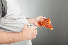 Man holding pizza slice and canned beverage Stock Images