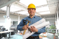 Man holding plans and tools. Inside a modern building Stock Photography