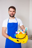 Man holding plastic bucket with bottles and brushes, gloves and. Detergents in the kitchen, on white background, set cleaning concept Stock Photography