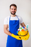Man holding plastic bucket with bottles and brushes, gloves and Stock Image
