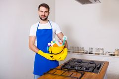 Man holding plastic bucket with bottles and brushes, gloves and. Detergents in the kitchen, on white background, set cleaning concept Royalty Free Stock Photos