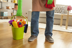 Man holding plastic bucket with detergents in room. Man holding plastic bucket  with detergents in room Stock Photography