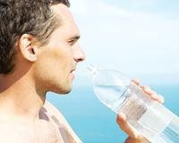 Man holding  plastic water bottle. A young man holding a plastic water bottle against the blue of the sea Stock Image
