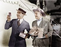 Man holding plates of sandwiches with a man looking at a film slide beside him royalty free stock photos