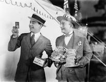 Man holding plates of sandwiches with a man looking at a film slide beside him. (All persons depicted are no longer living and no estate exists. Supplier grants stock photos