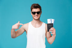 Man holding and pointing finger at passport with flying tickets. Happy smiling man in sunglasses holding and pointing finger at passport with flying tickets Stock Photography