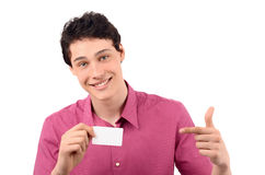 Man holding and pointing to a business card. Young business man smiling pointing to a white business card. Isolated on white background Stock Image