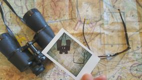 Man holding polaroid photo over a map stock image