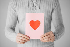 Man holding postcard with heart shape Royalty Free Stock Photo