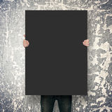 Poster mockup over grunge wall. Man holding poster mockup over grunge wall Royalty Free Stock Photo