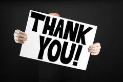 Man holding poster with thank you. In front of a black background Royalty Free Stock Images