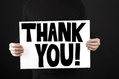Man holding poster with thank you. In front of a black background Stock Photo