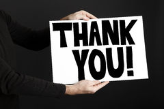 Man holding poster with thank you. In front of a black background Royalty Free Stock Photos