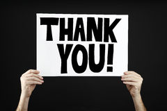 Man holding poster with thank you. In front of a black background Stock Photos