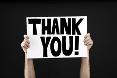 Man holding poster with thank you. In front of a black background Royalty Free Stock Image