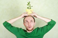 Man holding potted plant on his head Stock Photo