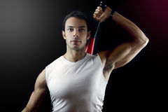 Man holding a power club behind his shoulder. A male doing a power club exercise seen holding it behind his shoulders on a black background Stock Image